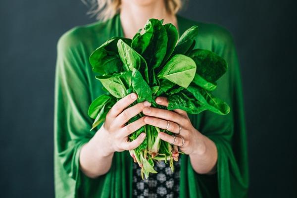 Mujer sosteniendo un manojo de hojas de espinaca
