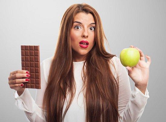 Mujer sosteniendo chocolate y manzana