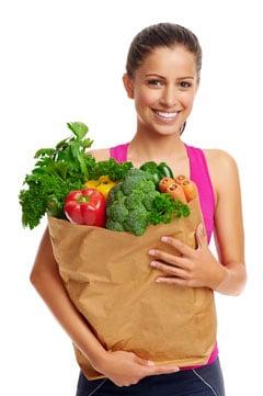 Mujer sosteniendo la bolsa de la compra llena de verduras saludables