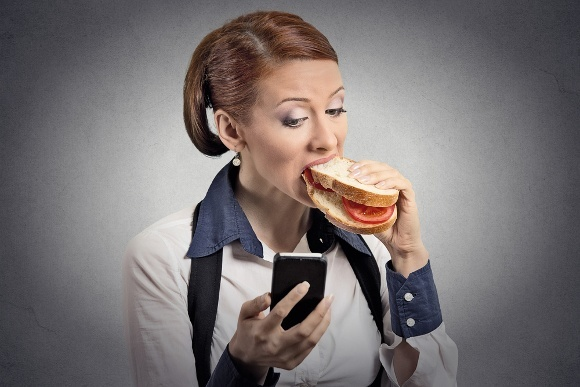 Mujer sosteniendo teléfono comiendo sándwich