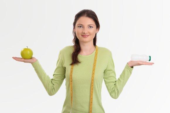 Mujer sosteniendo probióticos y manzana