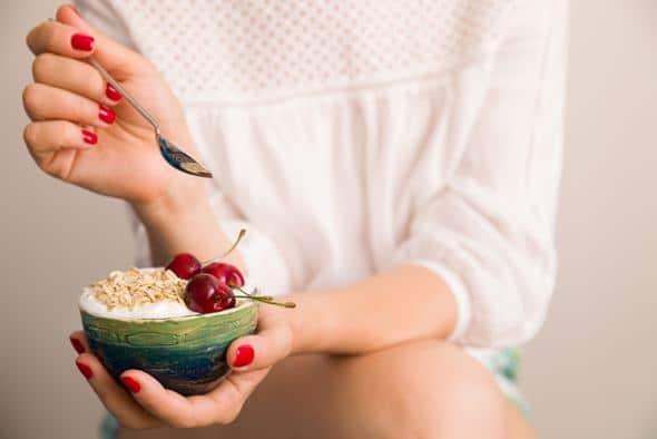 Mujer sosteniendo un tazón pequeño de avena, yogur y cerezas
