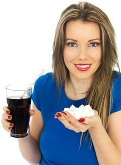Mujer sosteniendo refrescos y azúcar