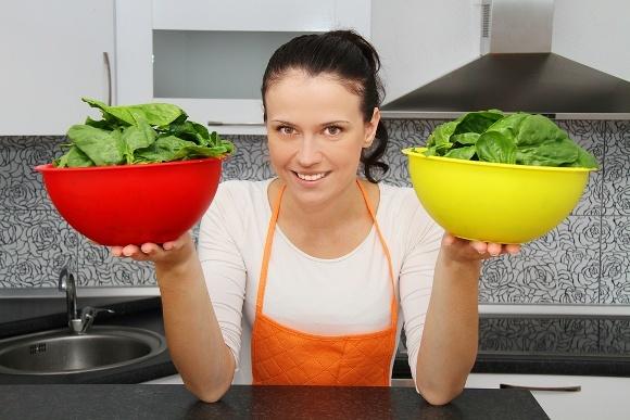 Mujer sosteniendo dos tazones de fuente de espinaca verde