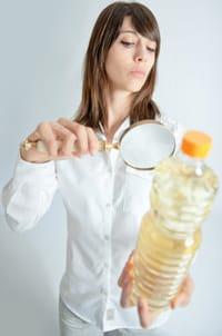 Mujer inspeccionando la botella de aceite con una lupa