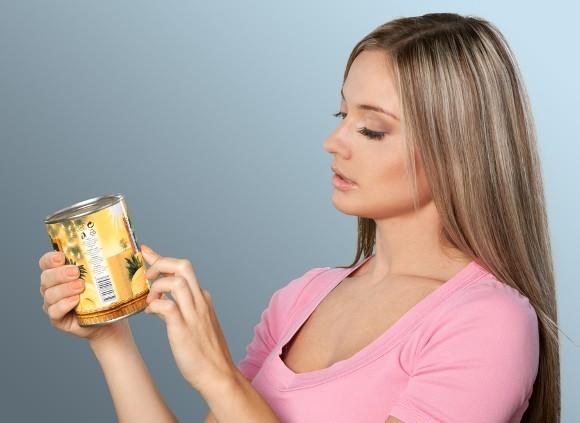 La mujer está examinando de cerca la etiqueta de los alimentos