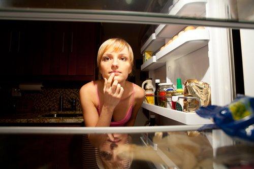 Mujer mirando dentro de una nevera