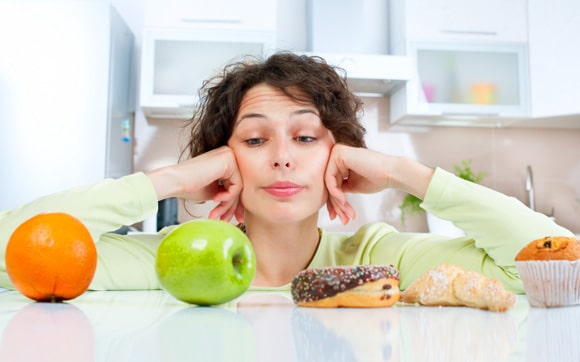 Mujer que elige entre fruta y comida chatarra