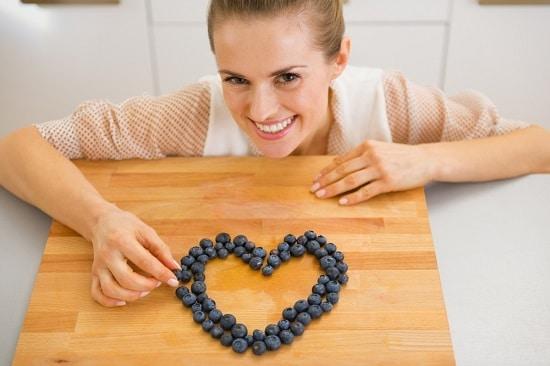 Mujer haciendo corazón con arándanos