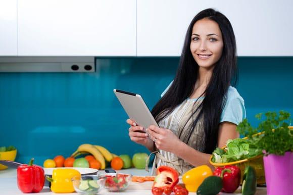 Mujer en tableta en cocina con frutas y verduras