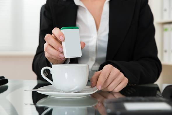 Mujer poniendo edulcorante en su café