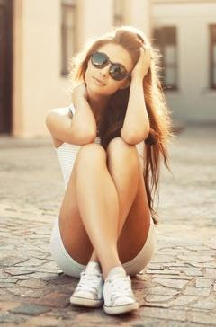Mujer sentada en la calle, al sol