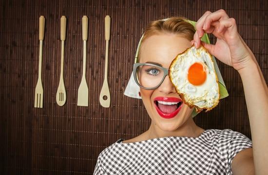 Mujer sonriendo y sosteniendo un huevo frito
