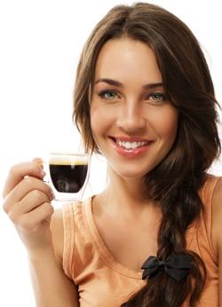 Mujer sonriendo con una pequeña taza de café