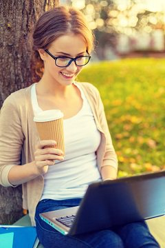 Mujer con café leyendo en la computadora portátil