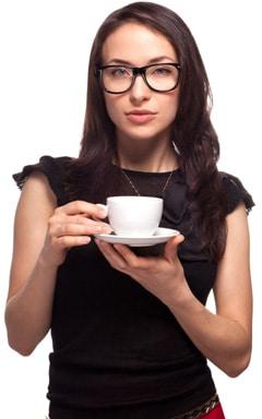 Mujer con gafas sosteniendo una taza de café