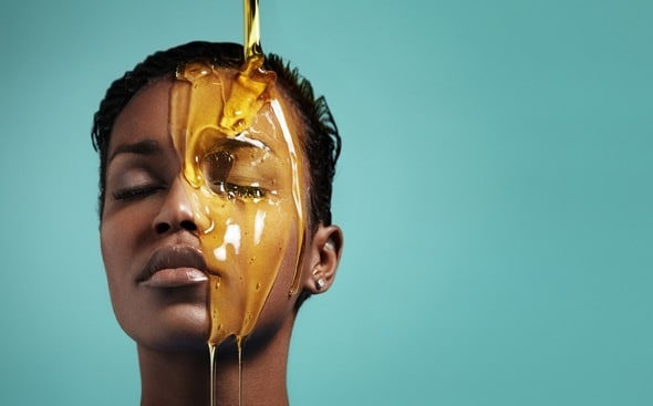 Mujer con miel goteando sobre la cara