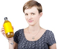 Mujer con pelo corto sosteniendo una botella de vinagre de sidra de manzana