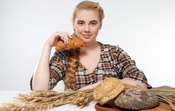 Mujer con mesa llena de panes de trigo