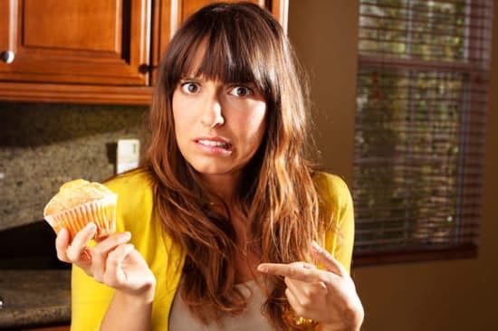 Mujer preguntándose si comer muffin
