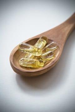 Cuchara de madera con cápsulas de vitamina D