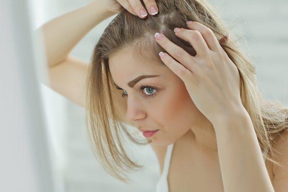 Joven rubia mirando su cuero cabelludo en el espejo