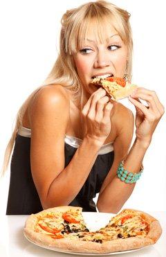 Joven mujer rubia comiendo pizza