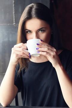 Joven morena bebiendo café