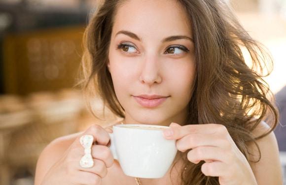 Joven morena disfrutando de una taza de café