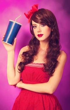 Joven morena sosteniendo un vaso de papel con soda