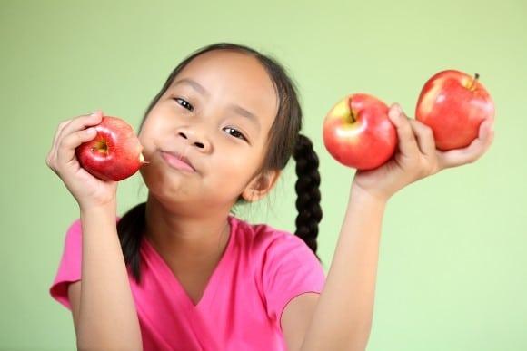 Niña joven, tenencia, tres manzanas