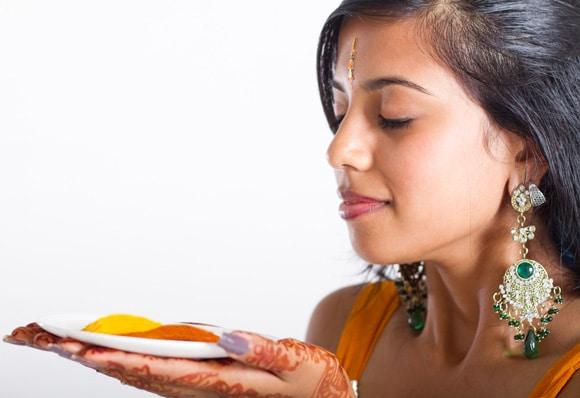 Joven india sosteniendo un plato con cúrcuma