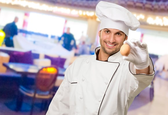 Joven chef sosteniendo un huevo