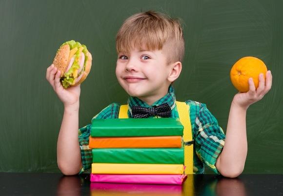 Niño de la escuela joven, tenencia, alimento