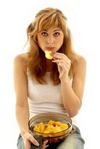 Mujer joven comiendo patatas fritas