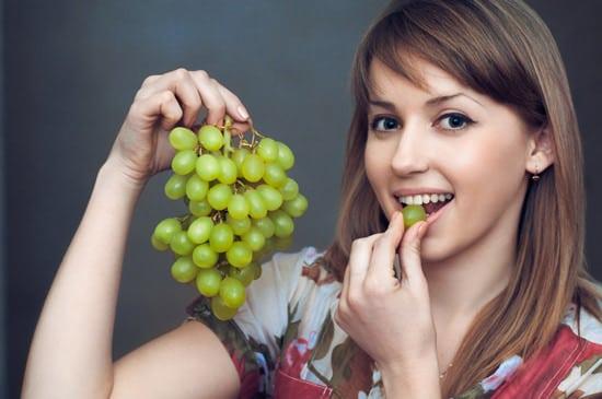 Mujer joven comiendo uvas verdes