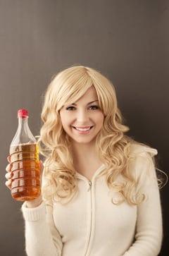 Mujer joven sosteniendo una botella de vinagre de sidra de manzana