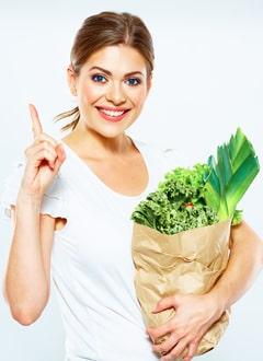 Mujer joven sosteniendo una bolsa de papel con verduras