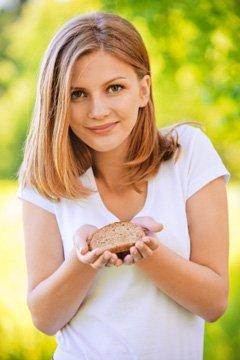Mujer joven sosteniendo una rebanada de pan