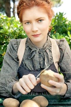 Mujer joven pelando patatas