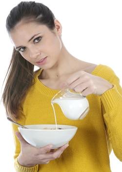 Mujer joven vertiendo leche en un recipiente