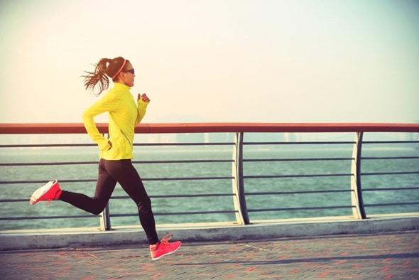 Mujer joven corriendo por la orilla del mar