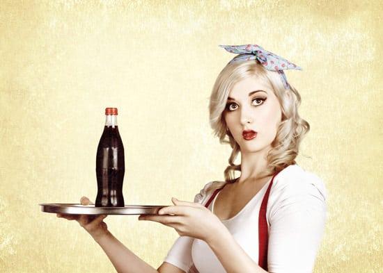 Mujer joven sirviendo Coca Cola