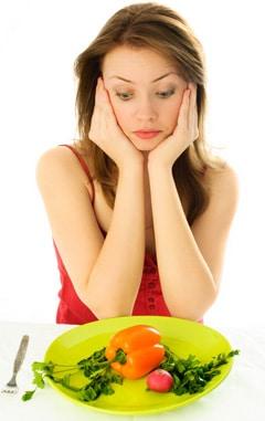 Mujer joven mirando un plato de verduras