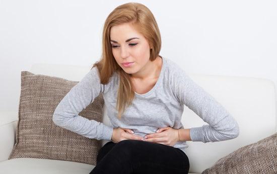Mujer joven con estómago hinchado